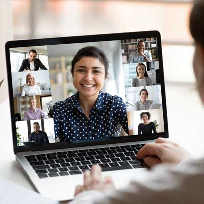 Woman leads video call, pc screen view over woman shoulder